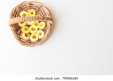 Directly above view of dried yellow everlasting daisies in small wicker basket on white table with copy space (selective focus)