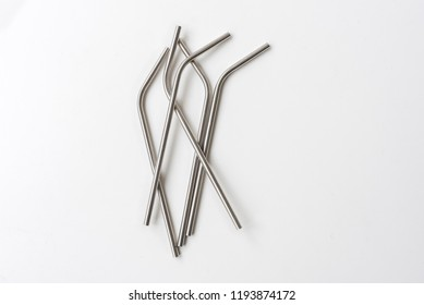 Directly above view of five metal straws randomly arranged on white background