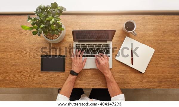 Directamente por encima de la vista de las manos humanas escribiendo en el portátil. Portátil, tableta digital, diario, taza de café y maceta en el escritorio. Hombre trabajando desde casa.
