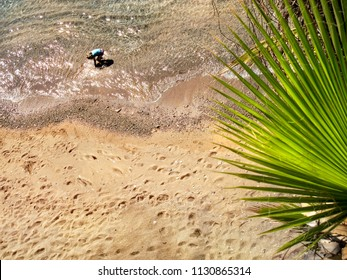 directly above view of little child playing on clear water beach on summer vacation