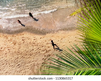 directly above view of little children playing on clear water beach on summer vacation