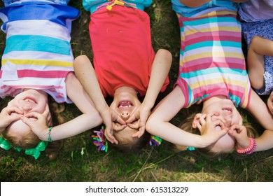 Directly above view of little girls lying on green grass in park and making funny faces with their fingers around eyes