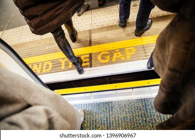 Directly above view at Mind the gap sign in London Underground metro train station with feets of pedestrians exiting entering metro train
