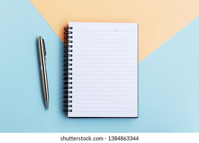 Directly above view of Notepad and pen on dual tones background