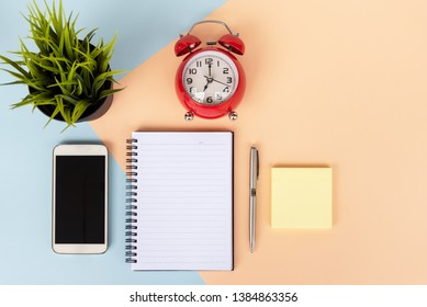 Directly above view of office desk with computer keyboard, cup of coffee,smart phone, alarm clock, sticky notes, pot of plant, note pad and pen on dual tones background