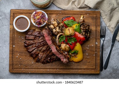 Directly above view of pork medallion with grilled vegetables, served on a wooden board