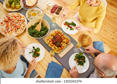 Directly above view of serious mature friends in casual clothing sitting at table and eating fresh salad, they enjoying delicious dinner