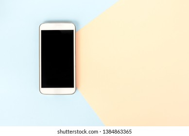 Directly above view of smart phone on dual tones background