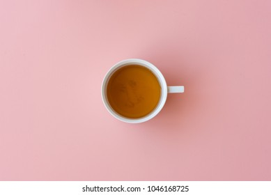 Directly above view of tea in cup on pink background
