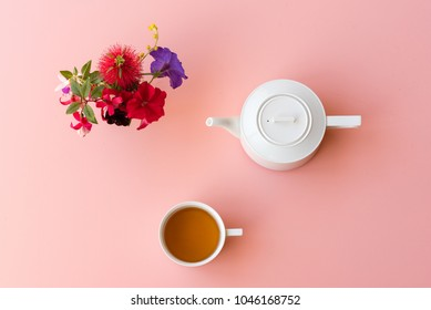 Directly above view of tea with white teapot and colorful flowers on pink background