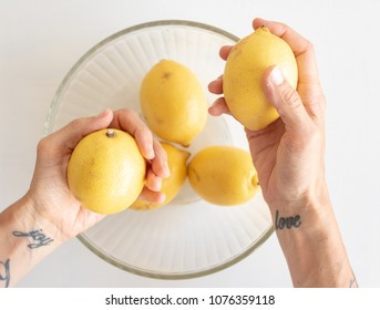 Directly above view of woman's hands holding lemons  above glass bowl on white table (selective focus)