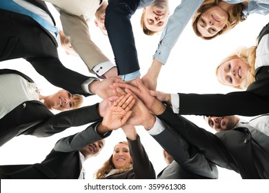 Directly below portrait of confident business team stacking hands against white background