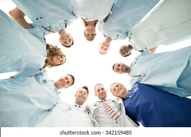 Directly below portrait of confident medical team standing in huddle against white background