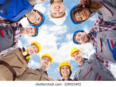 Directly below portrait of multiethnic architects standing in huddle against sky