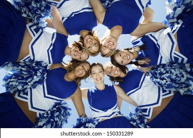 Directly below shot of happy cheerleaders forming huddle against sky