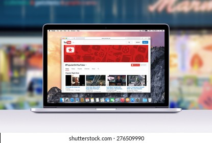 Directly front view of Apple 15 inch MacBook Pro Retina with an open tab in Safari which shows Youtube web page. Blurred shopping center space on the background. Varna, Bulgaria - November 03, 2013.