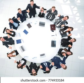 Director and business team sitting at the round table and holding each other's hands.