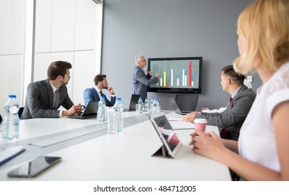Director of company present business plan while employees listen