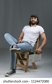 Director man wearing a casual outfit, sitting crossed legs on a wooden chair, holding capper board and smiling