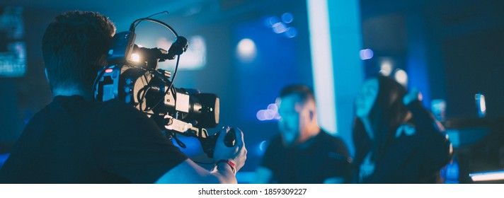 Director of photography with a camera in his hands on the set. Professional videographer at work on filming a movie, commercial or TV series. The filming process indoors, on a concert stage.