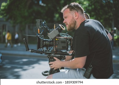 Director of photography with a camera in his hands on the set. Professional videographer at work on filming a movie, commercial or TV series. The filming process on the street, on location