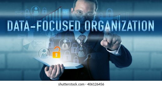 Director pressing DATA-FOCUSED ORGANIZATION on a virtual touch screen interface. Business strategy metaphor and information technology concept for enterprise decisions and operations driven by data.
