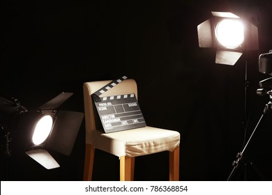 Director's chair with movie clapper under spotlight on filming location