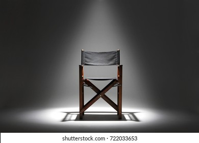 A directors chair sits against a plain dark background illuminated by a single overhead spotlight.
