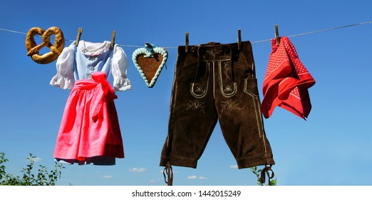 Dirndl and leather trousers are hanging on clothesline, banner