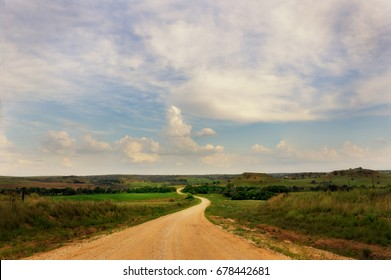 A dirt back country road winds through low hills in rural Kansas. Soft clouds fill the sky.
