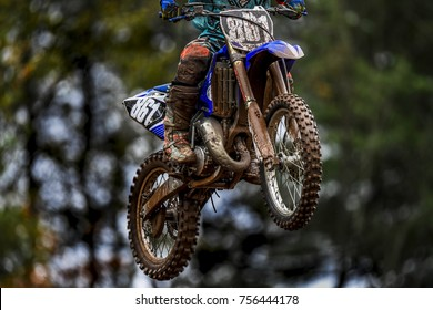 A dirt bike takes to the air during a motocross competition jump.
