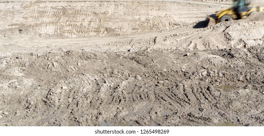 Dirt in construction area. Tractor tread tracks in soil. Blurred excavator moving in background.
