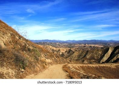 Dirt fire road leading through mountains, California