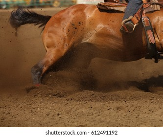 Dirt flying as a barrel racing horse goes into a skid.