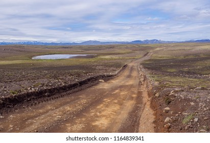 dirt mountain road in abandoned green landscape at Nature reserve Fjallabak in Iceland with  snow covered rhyolit mountain range, blue sky white clouds