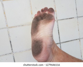 dirt on bottom of foot and toes with white tile floor