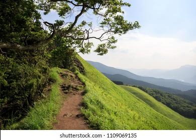 Dirt path along ridge at top of steep grassy hillside in Soni Kogen