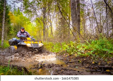 Dirt ride on an ATV. Off-road racing. A man without a helmet rides an ATV. Concept - a man is stuck. ATV stuck in the mud. From under the wheels - spray of water. Biker trying to get out of the mud.
