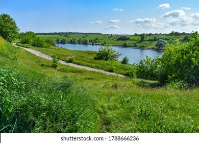 Dirt road among green hills on the shore of a pond with blue water. Bright natural panorama with a lake in the middle of juicy young grass on a spring-summer day