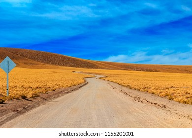 Dirt road in the Atacama Desert, with typical yellow colored vegetation, colorful blue sky with clouds and signaling plate.  Atacama Desert, Chile, South America, July 12, 2017.