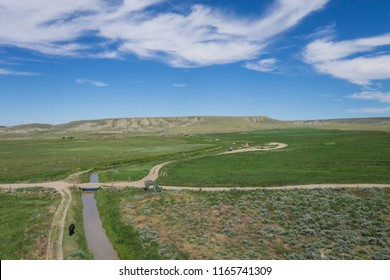 Dirt road and bridge cross an irrigation canal in the state of Wyoming in the American west.