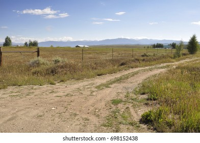 dirt road by a prairie in Colorado.  The Rockie Mountains are in the background.