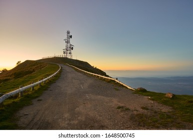 Dirt road to a communications tower on top of a mountain as the sun rises