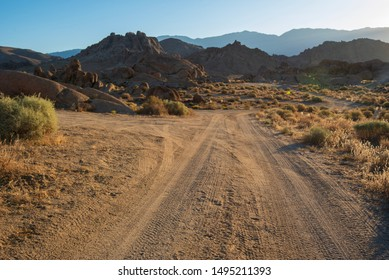 dirt road in desert landscape with rocky Alabama Hills and distant Sierra Nevada mountains