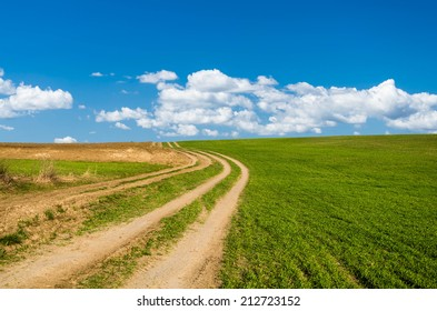 dirt road and green field