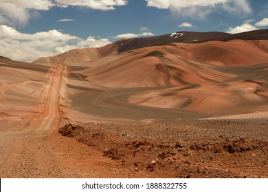 The dirt road high in the Andes mountains. Traveling along the route across the arid desert dunes and mountain range. The sand and death valley under a deep blue sky in La Rioja, Argentina.