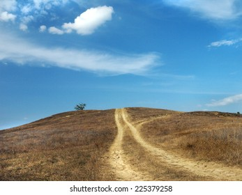 dirt road up the hill and blue sky