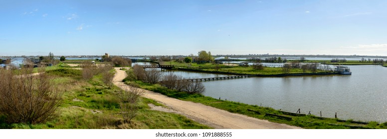 dirt road and lagoon view from watchtower, shot in bright spring sun light at Comacchio, Ferrara,  Italy