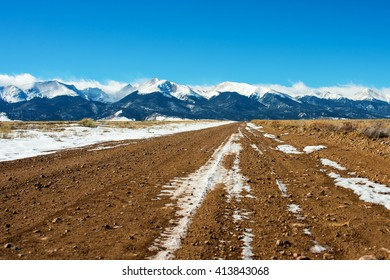 Dirt road leading up to the Sangre de Cristo mountain range in winter, Westcliffe, Colorado.