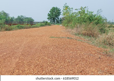 The dirt road is made of pebbles.